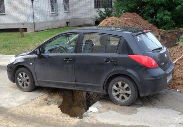 Яма под машиной на дороге