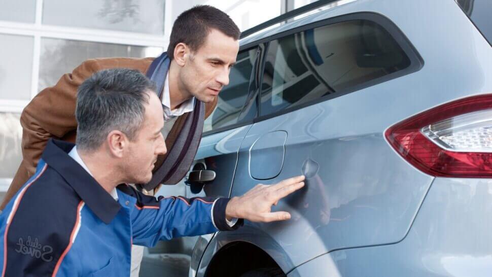 Мужчины смотрят на вмятину авто