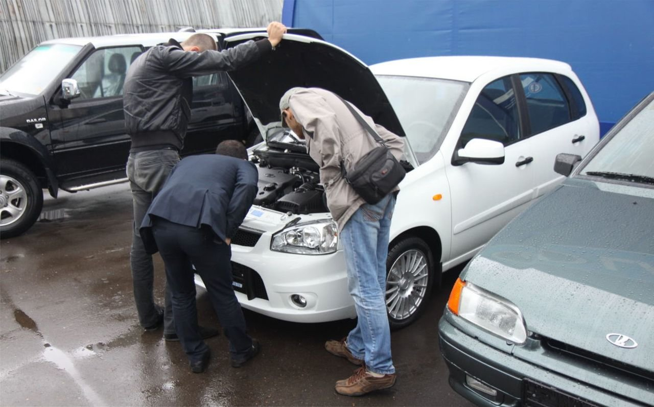 Мужчины смотрят под капот авто