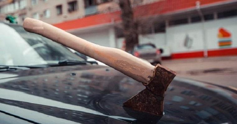 Топор в крышке капота авто