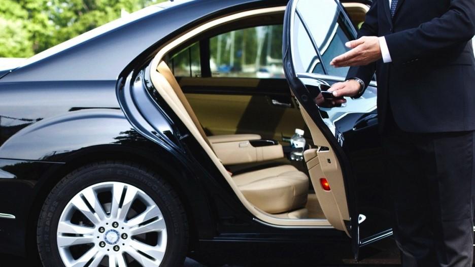 Мужчина в костюме открывает дверь автомобиля