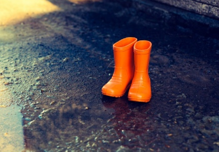Оранжевые резиновые сапоги на дороге