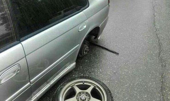 Машина без колеса на проезжей части