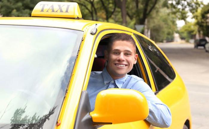 Таксист за рулем улыбается