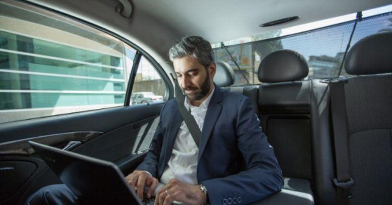 Мужчина на заднем сиденье с ноутбуком