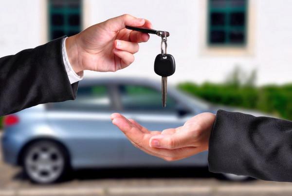 Ключ в руке и автомобиль