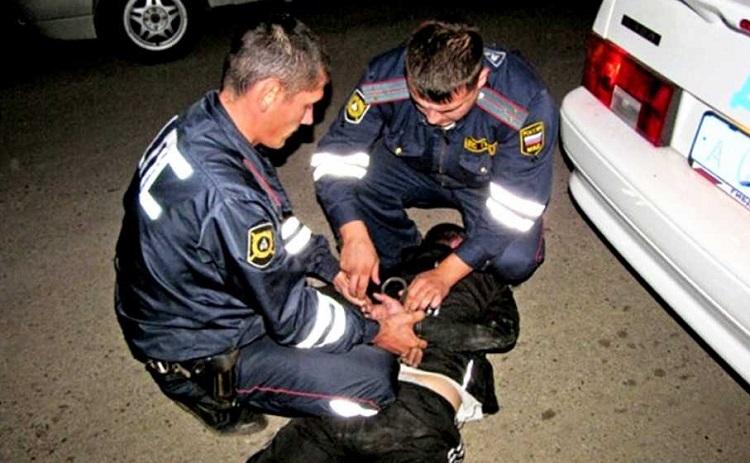 Сотрудники ДПС надевают наручники преступнику