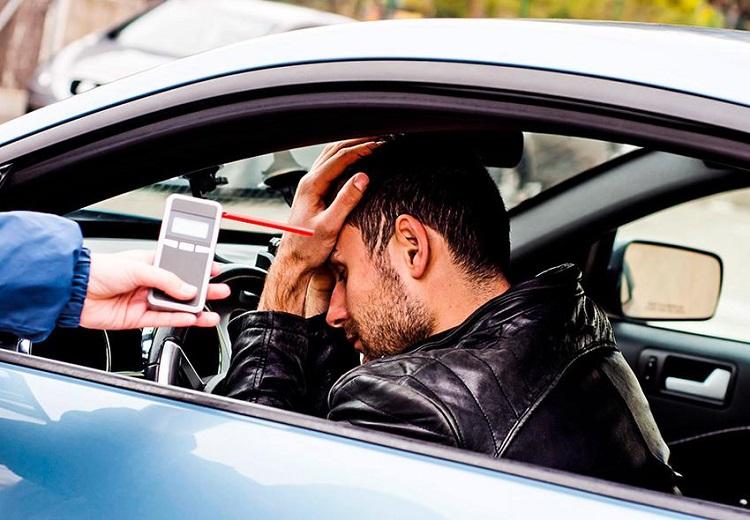 Водитель наклонил голову и алкотестер