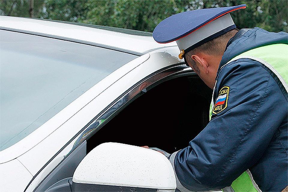 Сотрудник ГАИ заглядывает в авто