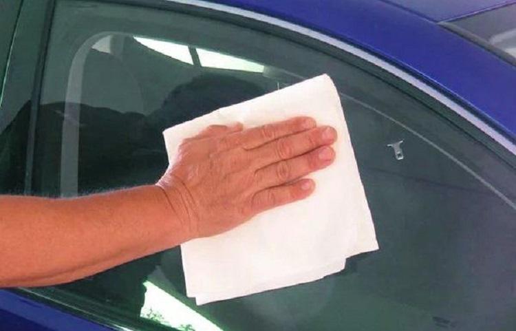 Человек протирает стекло авто салфеткой