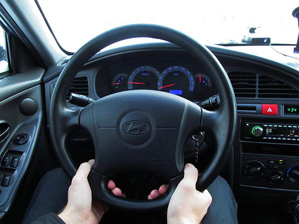 Руки водителя под рулевой колонкой