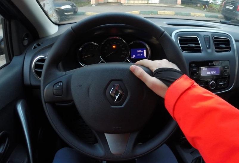 Правая рука водителя на рулевой колонке