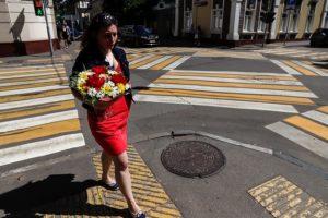 Девушка с цветами переходит дорогу