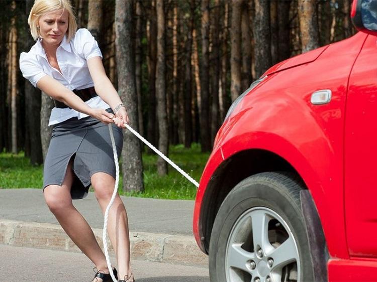Девушка тащит машину на тросе