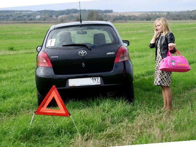 Девушка, авто и аварийный знак в поле