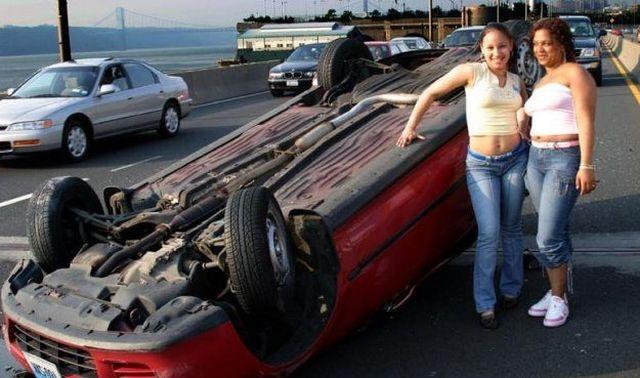 Девушки фотографируются у перевернутой машины