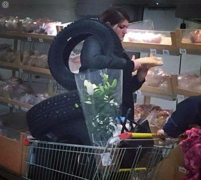 Девушка в супермаркете с шинами на плечах