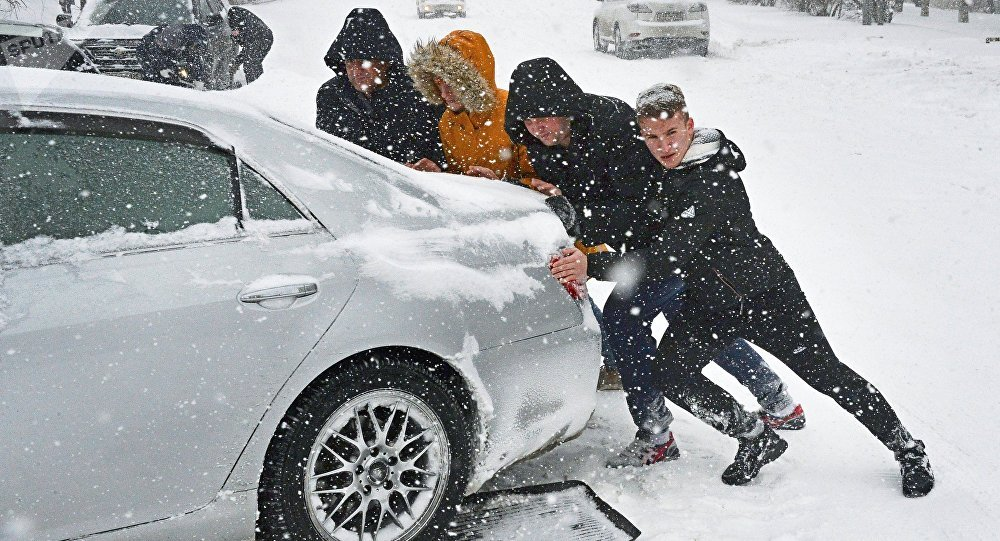 Люди толкают машину в снегу