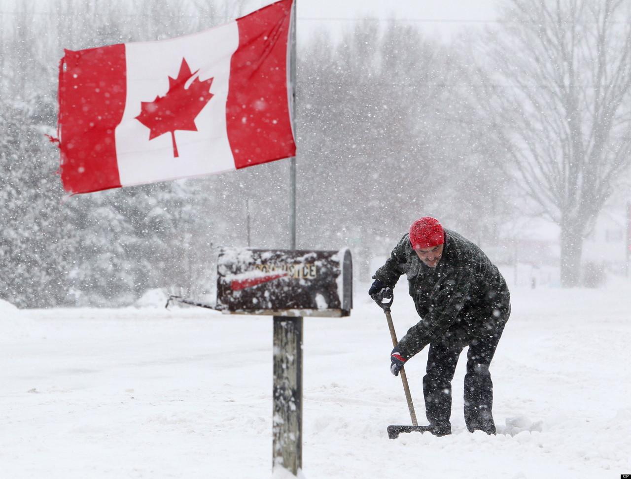 Канадский флаг и человек убирает снег