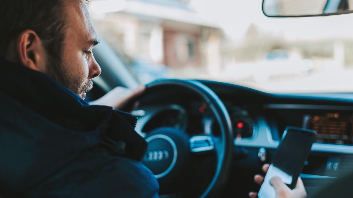 Водитель за рулем со смартфоном