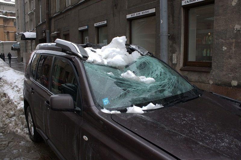 Смятая крыша авто от глыбы снега
