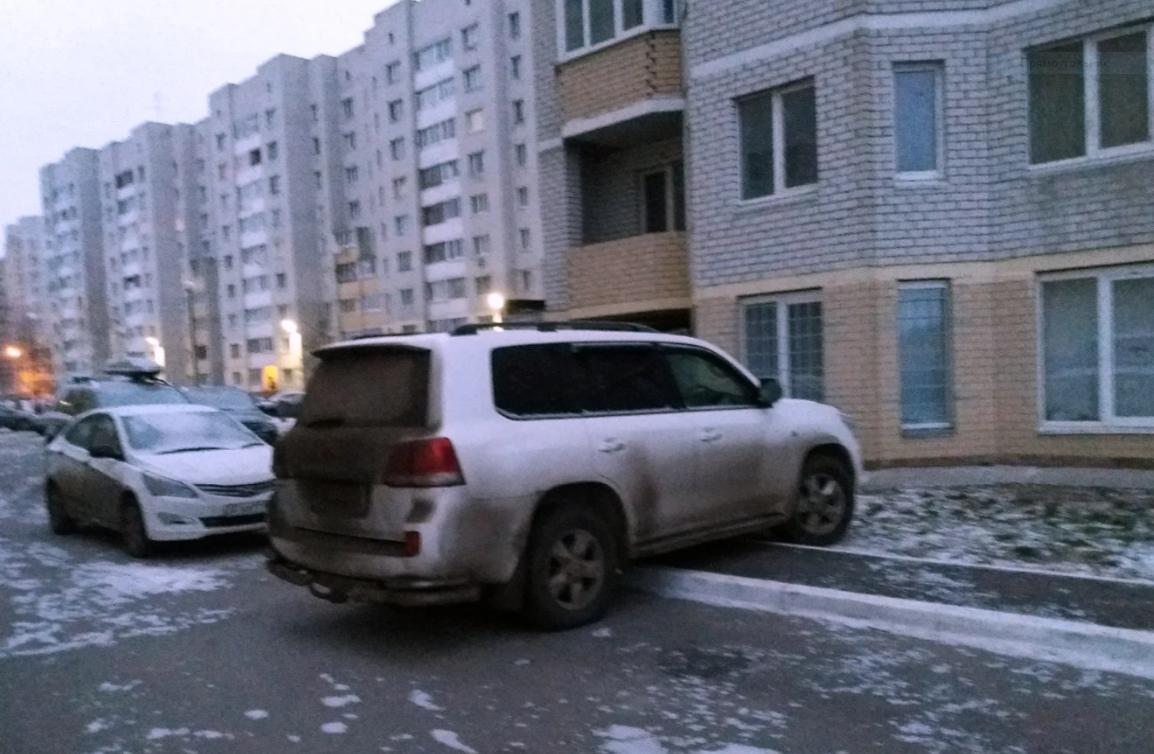 Машина припаркованная на газоне и тротуаре