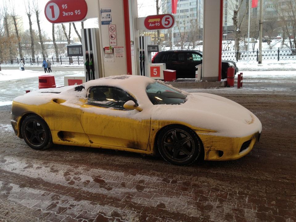 Желтая Феррари в снегу на заправке