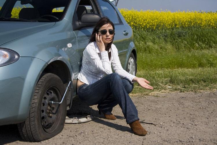 Девушка возле авто со сдутой шиной