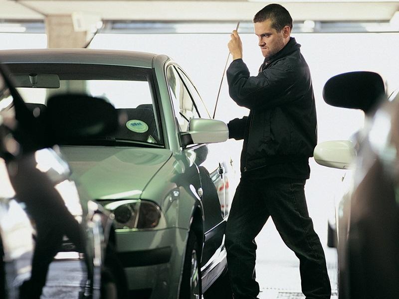 Человек прутом открывает дверь авто