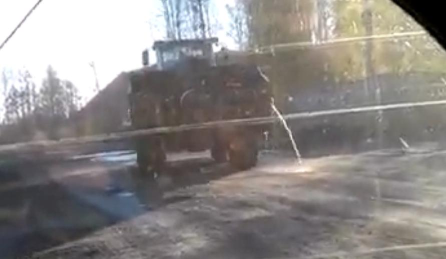 Трактор едет с водой в ковше