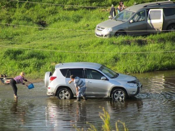 Люди моют авто в реке