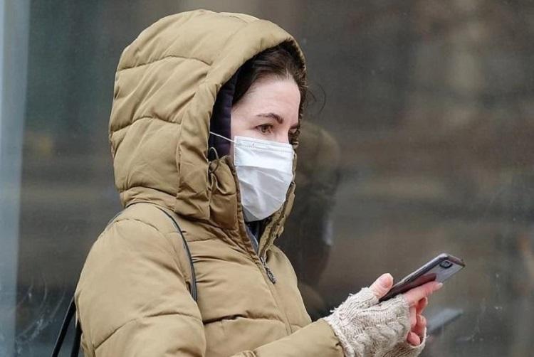 Девушка с телефоном в защитной маске